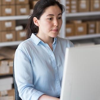 Zijaanzicht zakenvrouw die op laptop werkt