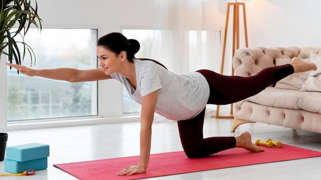 Zijaanzicht zwangere vrouw doet yoga thuis