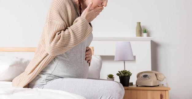 Zijaanzicht zwangere vrouw met ochtendmisselijkheid