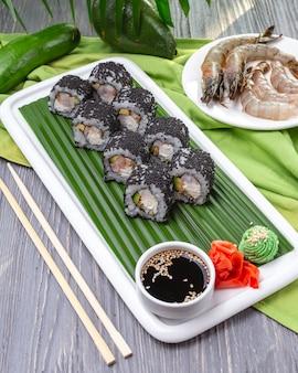 Zijaanzicht zwarte california roll tobiko kaviaar avocado roomkaas garnalen wasabi gember en sojasaus op een bord
