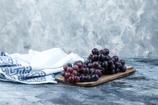 Zijaanzicht zwarte druiven met snijplank op grungy gips en keukendoek achtergrond. horizontaal