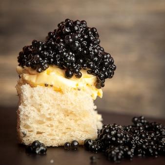 Zijaanzicht zwarte kaviaar met boter op brood op donkere achtergrond.