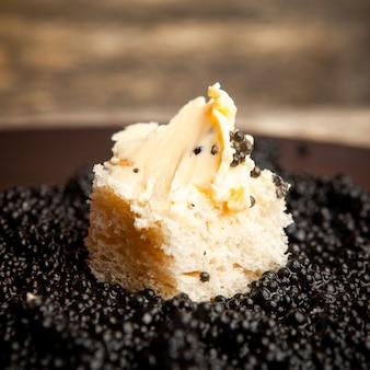 Zijaanzicht zwarte kaviaar met brood en boter op donkere achtergrond.
