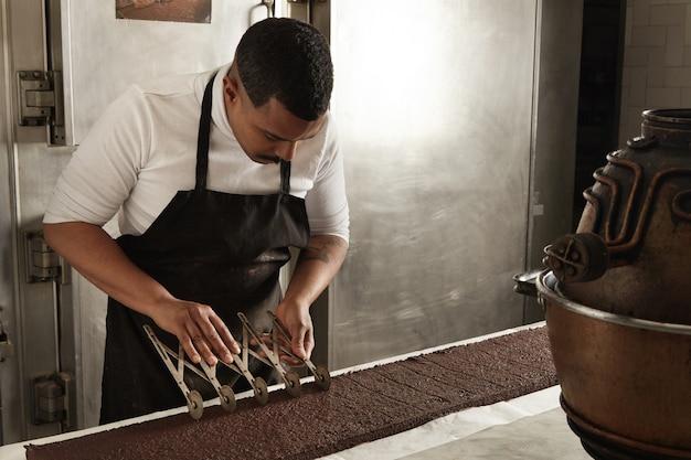 Zijaanzicht zwarte man chef gebruikt professionele vintage scheider om chocoladetaart op gelijke porties te splitsen voordat ze worden verpakt, ambachtelijk kookproces in zoetwaren