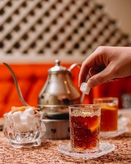 Zijaanzicht zwarte thee met schijfje citroen snoep en theepot op tafel