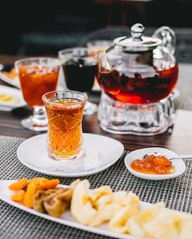 Zijaanzicht zwarte thee met snoep witte kersenjam en theepot op tafel