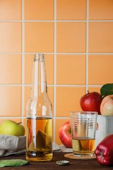 Zijaanzichtappelen in doos met appelsap op houten en oranje tegelachtergrond. verticale ruimte voor tekst