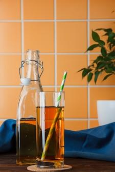 Zijaanzichtappelen in fles en glas met appelsap op houten en oranje tegelachtergrond. verticaal