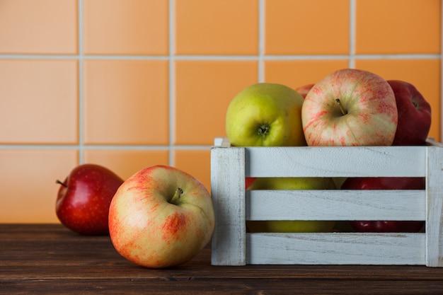 Zijaanzichtappelen in houten doos op oranje tegelachtergrond. horizontale ruimte voor tekst