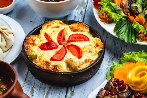 Zijaanzichtbraadpan met aardappelkaas en tomaat in een kleischotel