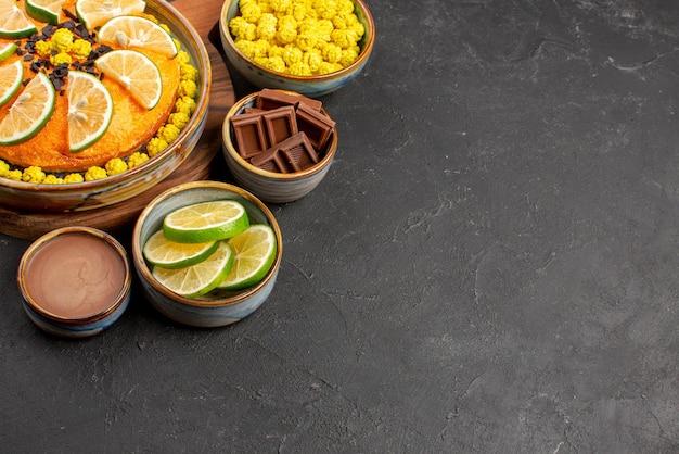Zijaanzichtcake en limoensnoepjes chocoladeroom en gesneden limoenen in kommen naast de smakelijke sinaasappelcake op tafel