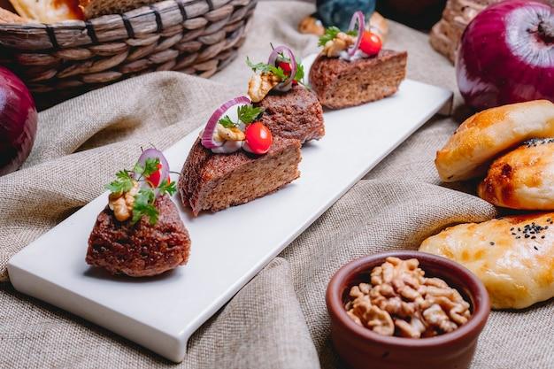 Zijaanzichtcake met gebakken gehakt ui tomaat greens en walnoten op tafel
