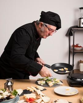 Zijaanzichtchef-kok in keuken het koken