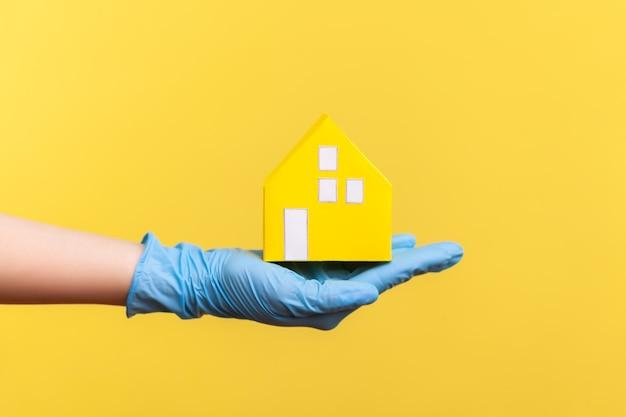 Zijaanzichtclose-up van menselijke hand in blauwe chirurgische handschoenen die gele document huisbuitenkant in hand houden.
