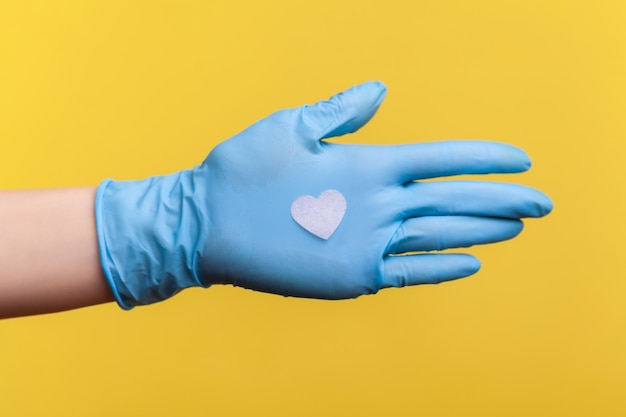 Zijaanzichtclose-up van menselijke hand in blauwe chirurgische handschoenen die kleine roze hartvorm in hand houden