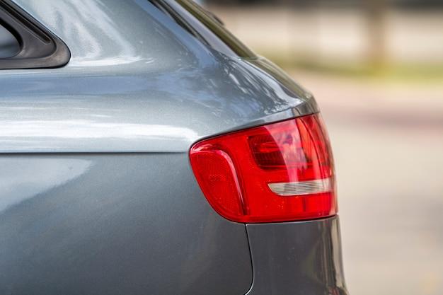 Zijaanzichtdetail van rode stoplichten van glanzende luxueuze zilveren auto