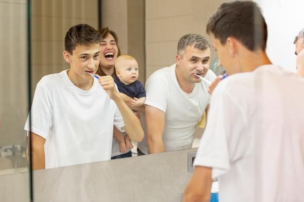 Zijaanzichtfamilie die in de spiegel kijkt