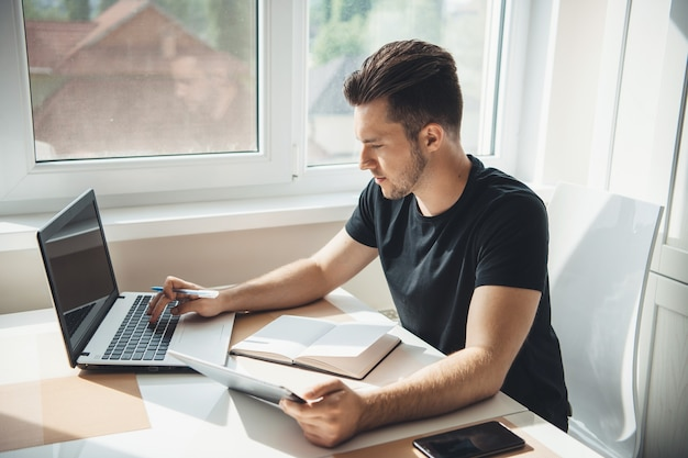 Zijaanzichtfoto van een blanke man die thuis op de laptop werkt met behulp van een boek en een tablet