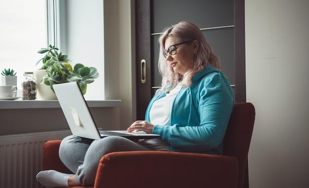 Zijaanzichtfoto van een blanke senior vrouw die iets op de laptop typt terwijl ze een bril en vrijetijdskleding in een fauteuil draagt