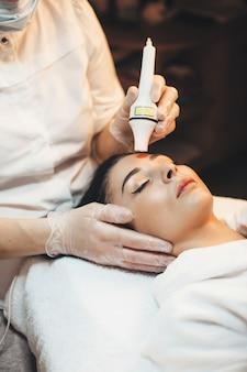 Zijaanzichtfoto van een blanke vrouw die bij kuuroordsalon ligt met een gezichtsbehandeling tegen veroudering met moderne apparatuur