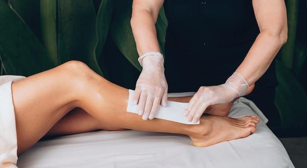 Zijaanzichtfoto van een blanke vrouw die een kuuroordprocedure van het ontharen van het beenhaar heeft