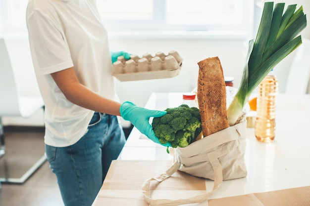Zijaanzichtfoto van een blanke vrouw die producten uitpakt die medische handschoenen thuis dragen