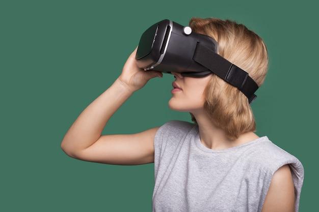 Zijaanzichtfoto van een blanke vrouw met blond haar die nieuwe vr-headset probeert op een groene studiomuur