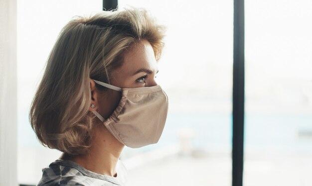 Zijaanzichtfoto van een blonde vrouw met medisch masker op gezicht dat dichtbij het raam zit