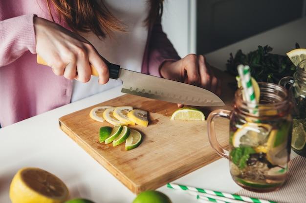 Zijaanzichtfoto van een gemberdame die mojito thuis voorbereiden die citroen met een mes snijden