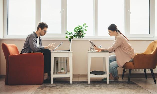 Zijaanzichtfoto van een kaukasisch zakenpaar dat van huis aan de computers werkt en iets schrijft dichtbij het venster