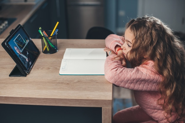 Zijaanzichtfoto van een moe kaukasisch meisje dat naar de leraar op de tablet kijkt en de online lessen luistert