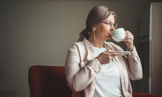 Zijaanzichtfoto van een oudere vrouw die een kopje thee drinkt terwijl ze door het raam van binnen uit het huis kijkt