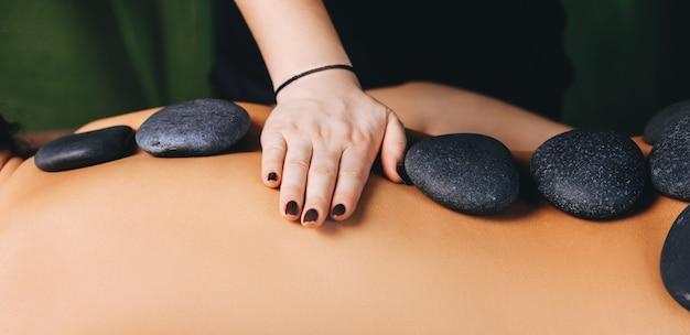 Zijaanzichtfoto van een spa-procedure van massage met stenen op de rug van de cliënt
