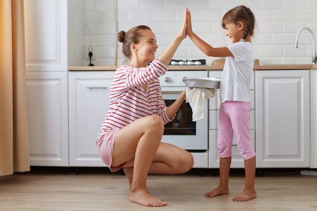 Zijaanzichtfoto van een vrolijke charmante mama en een klein kind die high-five geven in een lichte keuken, samen een heerlijk dessert bakken, familie die casual kleding draagt, thuis poseren.