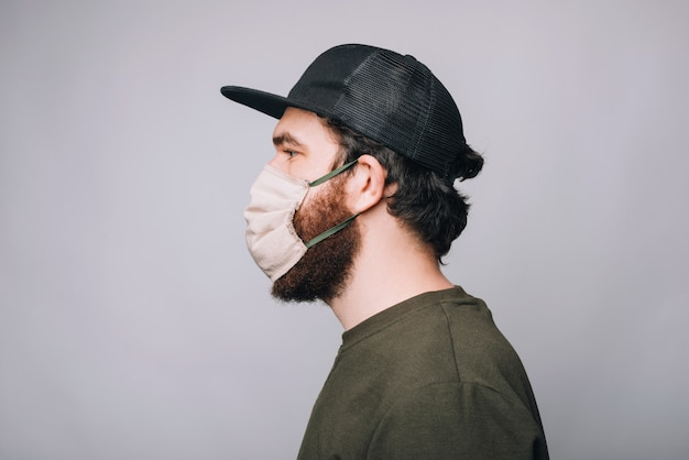Zijaanzichtfoto van het gebaarde hipster man wering masker voor anti covid bescherming