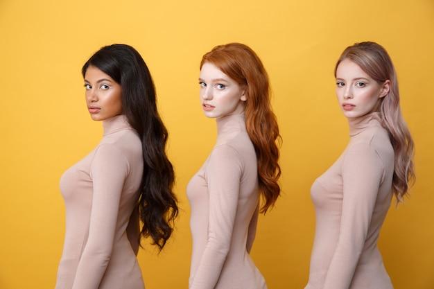 Zijaanzichtfoto van jonge ernstige drie dames