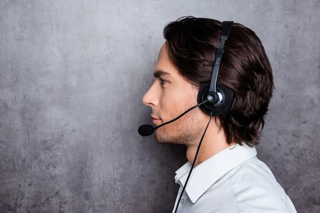 Zijaanzichtfoto van knappe jonge exploitant in callcenter met hoofdtelefoons