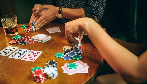 Zijaanzichtfoto van mannelijke en vrouwelijke vrienden die aan houten tafel zitten. mannen en vrouwen die kaartspel spelen. handen met alcoholclose-up.