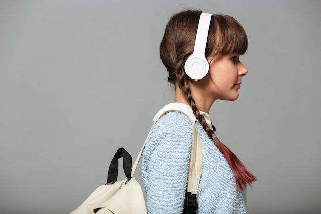 Zijaanzichtfoto van meisje het luisteren muziek met hoofdtelefoons