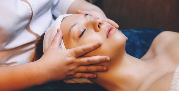 Zijaanzichtfoto van mooie blanke vrouw met een ontspannende gezichtsmassage in de spa salon