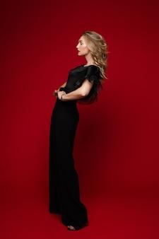 Zijaanzichtfoto van stijlvolle jonge vrouw in zwarte outfit poseren in, geïsoleerd op rode muur