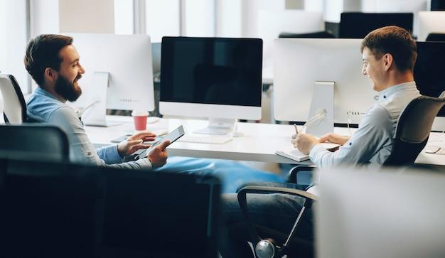 Zijaanzichtfoto van twee mannen die een zakelijke bespreking hebben in hun kantoor terwijl ze een tablet gebruiken