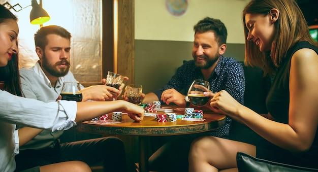 Zijaanzichtfoto van vrienden die aan houten tafel zitten. vrienden hebben plezier tijdens het spelen van bordspel.