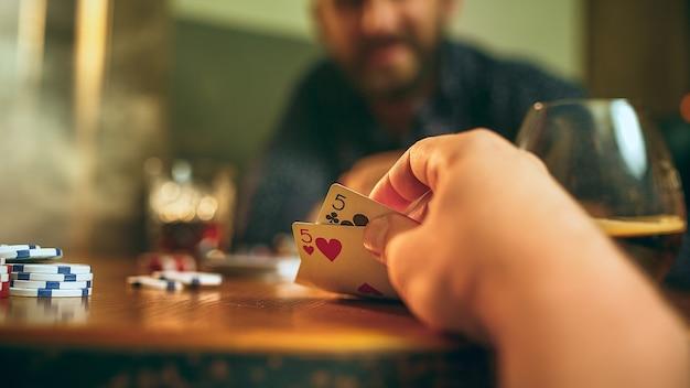 Zijaanzichtfoto van vrienden die aan houten tafel zitten.