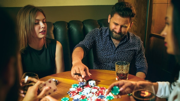 Zijaanzichtfoto van vrienden die bij houten lijst zitten. vrienden plezier tijdens het spelen van bordspel.