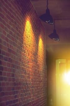Zijaanzichtgang en lamp lichte vlek op uitstekende de bouwbakstenen muur