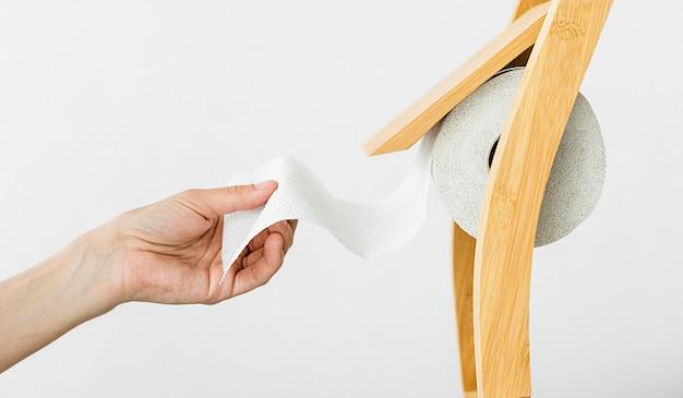Zijaanzichthand die toiletpapier trekken