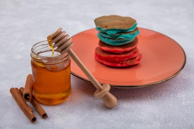 Zijaanzichthoning in een pot met een houten lepel kaneel en kleurrijke pannenkoeken op een oranje plaat op een witte achtergrond