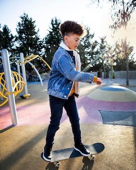 Zijaanzichtjongen die bij het park skateboarden