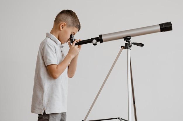 Zijaanzichtjongen die een telescoop in de klas gebruikt